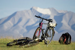 Bicycles in mountains. Two bicycles (one costs, another lies) and a backpack on a grass brightly shined by the sun. On a background - mountain and a glacier. One Royalty Free Stock Photos