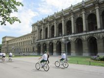 Bicycles. Munich bicycles people riding bicycles near monument Stock Images