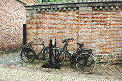 Bicycles near a brick wall Stock Images