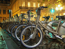 Bicycles in Paris. Bicycles in lines waiting to be picked at the station for a romantic ride in Paris city by night. Public Velib bicycle sharing system, with Royalty Free Stock Photos