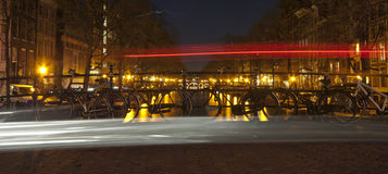 Bicycles parked on bridge in Amsterdam at night Stock Photo