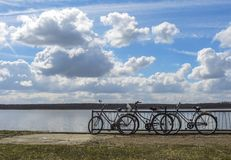 3 bicycles parked beside the lake on a clear yet cloudy autumn day stock images