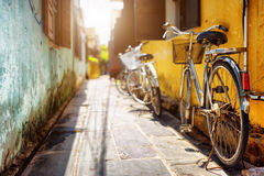 Bicycles parked near yellow wall of old house on sunny street Royalty Free Stock Photography