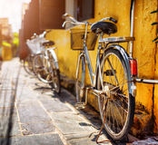 Bicycles parked near yellow wall on sunny street in summer Royalty Free Stock Photo