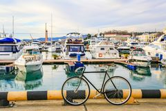 Bicycles parked on pier. Motor boats and luxury yachts docked in sea port. City street and blue water. Summer holiday vacation. Urban landscape. Travel concept stock photo