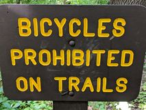Bicycles prohibited on trails sign, yellow letters on brown sign stock photo