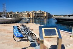 Bicycles on the quayside, Vittoriosa. Plaque for the Maltese Prime Minister Lawrence Gonzi along the waterfront with hire cycles to the rear and views of the Stock Photo