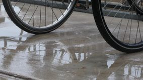 Bicycles in the rain. Rain falling on parked bicycles and pavement stock video