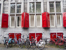 Bicycles and red shutters Stock Photos