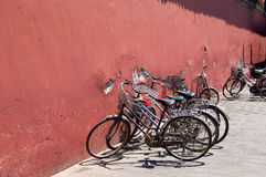 Bicycles beside red wall Stock Photography