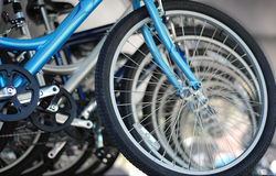 Bicycles in a Row. Close crop of numerous Blue Bicycles lined up and fading into the background. Selective focus is on the bottom of the front tire, on the bar Royalty Free Stock Image