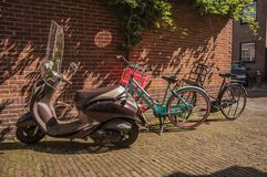 Bicycles and scooter in front of the bricked wall and door on sunny day at Weesp. royalty free stock image