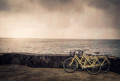 Bicycles by the sea. Two old retro vintage bicycles rested on a stone wall on the seaside in Lanzarote, Canary Islands, Spain Royalty Free Stock Photos