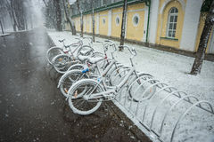 Bicycles smoothly covered with fresh snow after weather phenomen Royalty Free Stock Image