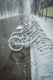 Bicycles smoothly covered with fresh snow after weather phenomen Stock Photos