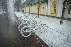 Bicycles smoothly covered with fresh snow after weather phenomen. Scenic view of a row of bicycles smoothly covered with fresh snow after weather phenomena Stock Photos