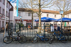 Bicycles stand in front of a beergarden. While its owners sit in the terrace Royalty Free Stock Photography