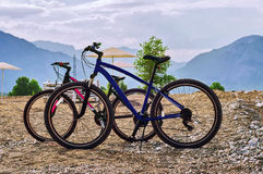 Bicycles standing on the beach. Two bicycles standing on the beach at mountains background Royalty Free Stock Image