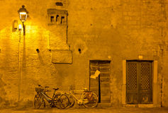 Bicycles under a Streetlamp in Grado at Night Stock Image
