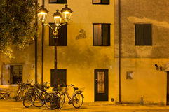 Bicycles under Streetlamps in Grado at Night Royalty Free Stock Photography