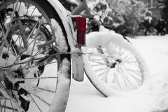Bicycles wheels in a snow in a bicycle parking. stock photos