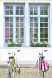 Bicycles and white house with blue windows Royalty Free Stock Photography