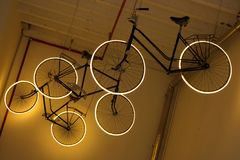 Bicycles with white lighting wheels under ceiling. City modern transport design. Sport vehicle Stock Image
