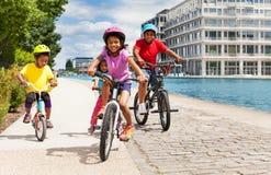 Bicyclette africaine mignonne d'équitation de fille avec ses amis Photo libre de droits