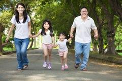 Bicyclette asiatique heureuse d'équitation de famille Photographie stock libre de droits