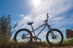 Bicyclette blanche au bord de la route rural contre un ciel bleu ensoleillé avec des nuages images libres de droits