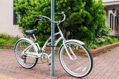 Bicyclette blanche verrouillée à un courrier de signe Images stock
