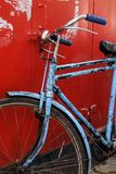Bicyclette bleue de vintage sur le fond rouge Photo stock