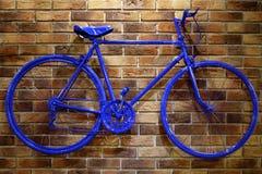Bicyclette bleue sur un mur de briques photo libre de droits