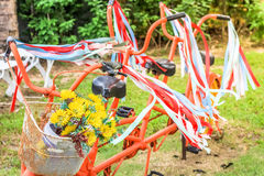 Bicyclette classique de style ancien avec le ruban rouge et blanc là-dessus et la fleur sur le panier Photos stock