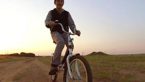 Bicyclette d'équitation d'adolescent de garçon La bicyclette d'équitation d'adolescent de garçon va à la nature le long de la vid Photos libres de droits