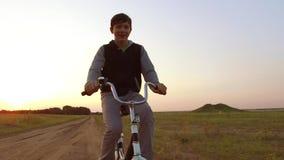 Bicyclette d'équitation d'adolescent de garçon La bicyclette d'équitation d'adolescent de garçon va à la nature le long de la vid Photographie stock
