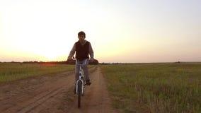 Bicyclette d'équitation d'adolescent de garçon La bicyclette d'équitation d'adolescent de garçon va à la nature le long de la vid Images libres de droits