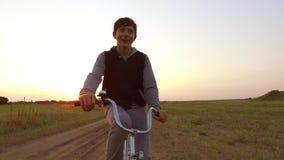 Bicyclette d'équitation d'adolescent de garçon La bicyclette d'équitation d'adolescent de garçon va à la nature le long de la vid Photo stock
