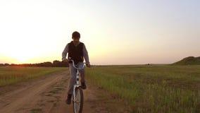 Bicyclette d'équitation d'adolescent de garçon La bicyclette d'équitation d'adolescent de garçon va à la nature le long de la vid Image stock