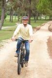 Bicyclette d'équitation d'homme aîné en stationnement Photographie stock