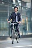 Bicyclette d'équitation d'homme d'affaires par la construction image libre de droits