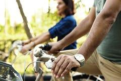 Bicyclette d'équitation de couples ensemble dans la jungle Photo stock