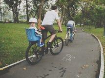 Bicyclette d'équitation de famille en parc sur le concept de vacances Images stock
