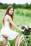 Bicyclette d'équitation de femme dans le domaine de wildflower Photographie stock libre de droits
