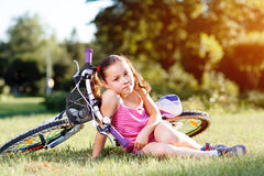 Bicyclette d'équitation de fille d'enfant sur le coucher du soleil d'été en parc Photos stock