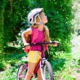 Bicyclette d'équitation de fille d'enfants dans la forêt Photo stock