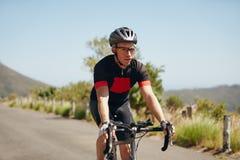 Bicyclette d'équitation de jeune homme sur la route ouverte Photographie stock