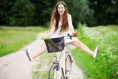 Bicyclette d'équitation de femme avec ses pattes dans le ciel Images libres de droits