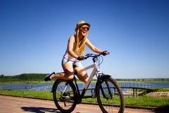 Bicyclette d'équitation de femme avec ses pattes dans le ciel Photographie stock