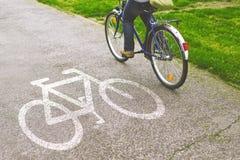 Bicyclette d'équitation de femme sur un chemin de vélo Photographie stock